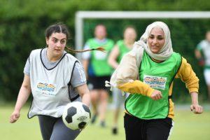 Zwei junge Frauen laufen auf einem Sportplatz einem Fußball hinterher.
