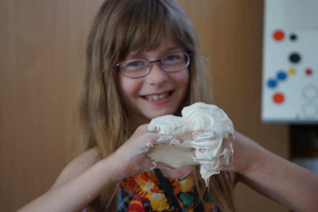 Ein Mädchen lächelt in die Kamera während es eine cremige Masse an seinen Händen hat..