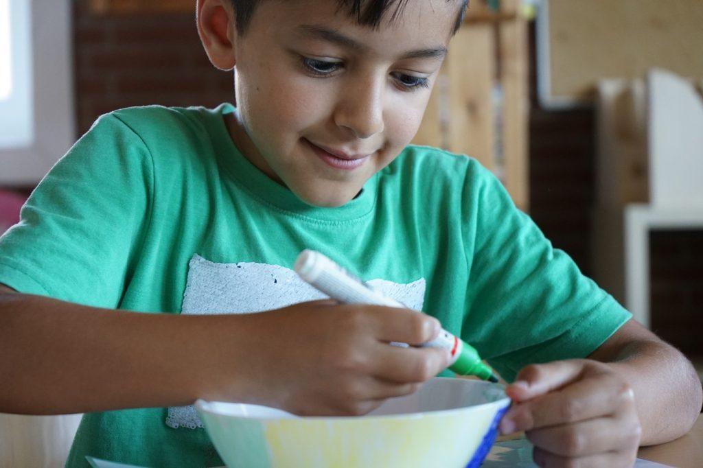 Ein Junge bemalt eine Schüssel.