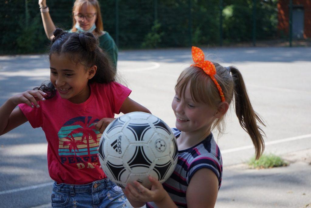 Zwei Mädchen lächeln im Vordergrund des Bildes. Das eine Mädchen hält einen Fußball in den Händen.