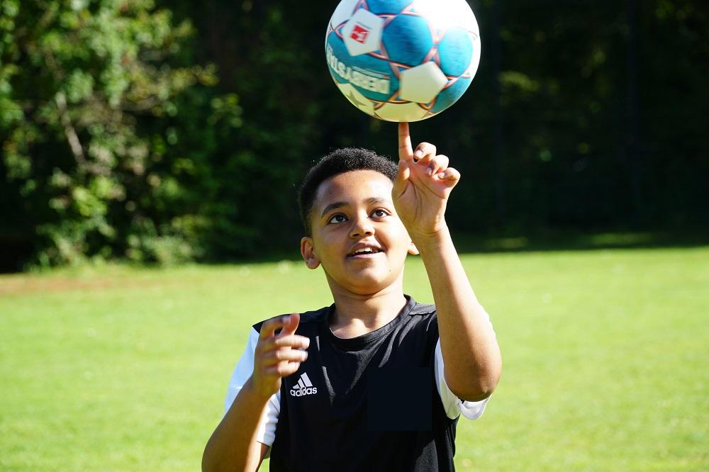 Ein Junge im schwarzen Sport-T-Shirt balanciert einen Fußball auf seinem linken Zeigefinger.